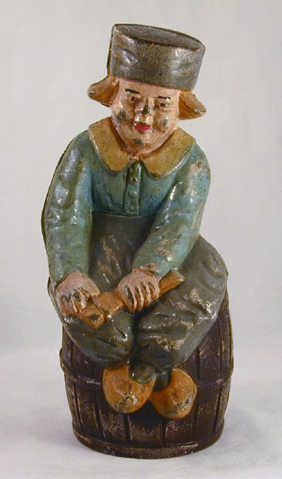 Description: This is a nice large and heavy painted cast iron penny bank in the form of a boy sitting on a barrel while holding something in his hand (He is actually whittling a piece of wood). The ba