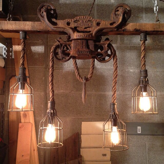 Hay trolley chandelier. Trolley, from the late 1800's, displays Edison bulbs on barn rope with light bulb cages.