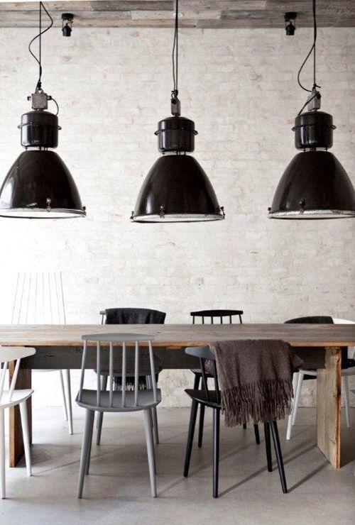 Lamparas industriales de gran escala, combinadas con una mesa rústica y varios estilos de sillas tipo shaker de arts and crafts.