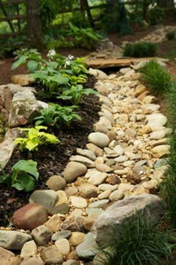 Dry creek beds aren't just for guiding the natural water flow from your property, they can also be used as a unique way to frame a flower bed. Scaling down and making a narrow bed of rocks such as this adds interest, helps keep water where it should be, and boxes in your plants.