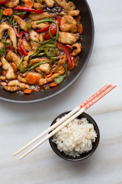 Sarten con el polloy las verduras con gran colorido y un cuenco de arroz con 2 palillos chinos