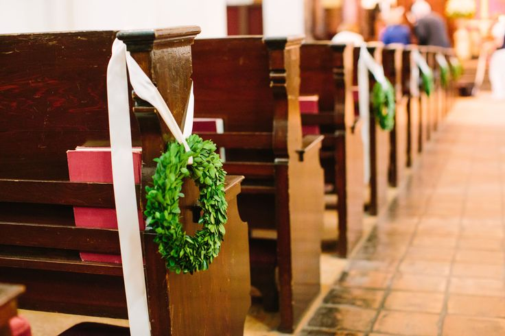 the chapel aisle is dressed and ready for the bride with fresh green boxwood wreaths tied to the pews with cream satin ribbon.