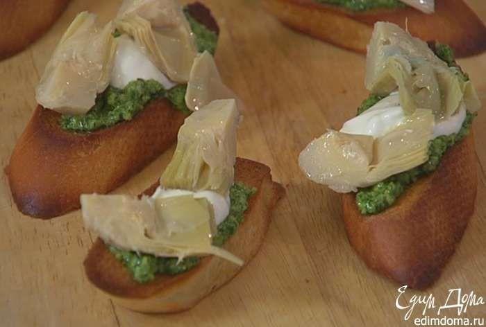 Смазать подсушенный хлеб соусом песто, сверху выложить понемногу сметаны и кусочки артишоков.