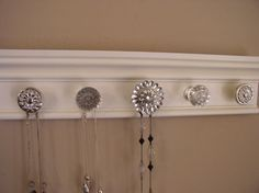 Jewelry organizer. This  wall rack  necklace hanger features a rhinestone center  & 5 knobs total on off  white finished 15 inches long