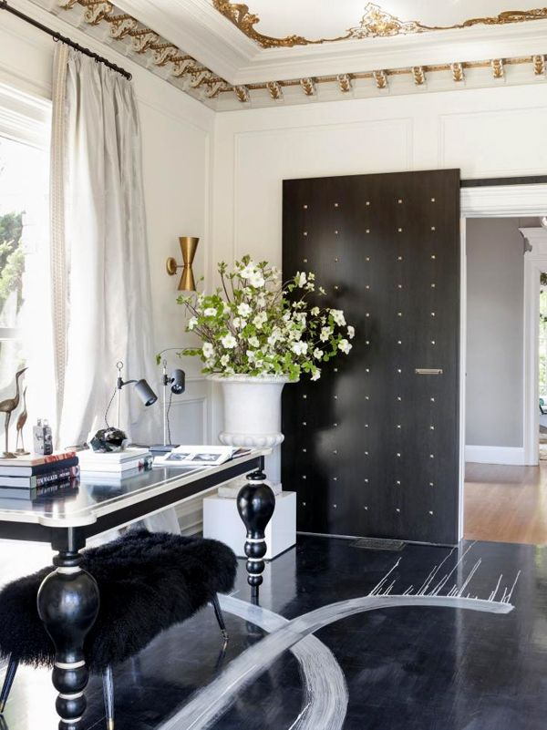 Mongolian sheepskin bench tucks under a vintage desk from Coup d'Etat, and ebonized barn doors, studded in bronze pyramids, mark the a stylish threshold to one very chic room. l DPAGES BLOG
