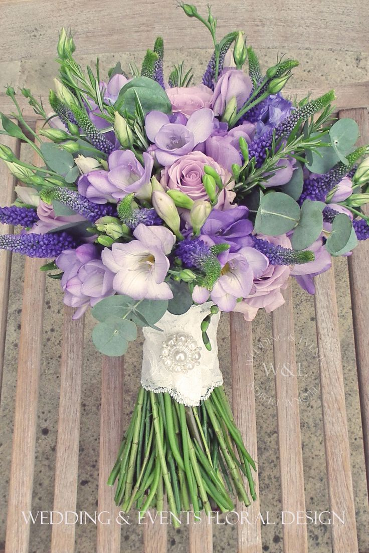 Purple lisianthus, blue roses, purple veronica, lavender freesia with eucalyptus.