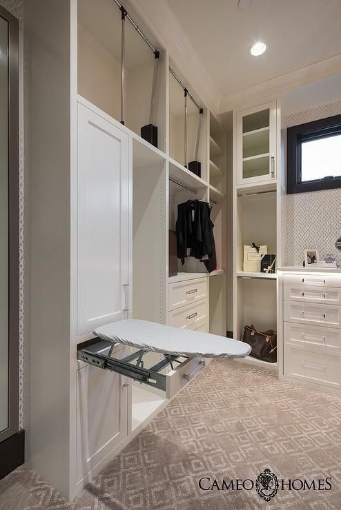 Large walk in closet features white built ins boasting white shaker cabinet doors accented with glass and nickel pulls, a drop down ironing board, bag shelves, glass front upper cabinets, and a built in white dresser sat on a gray diamond print rug under a black window framed by Schumacher Summer Palace Fret Wallpaper it by recessed lighting.