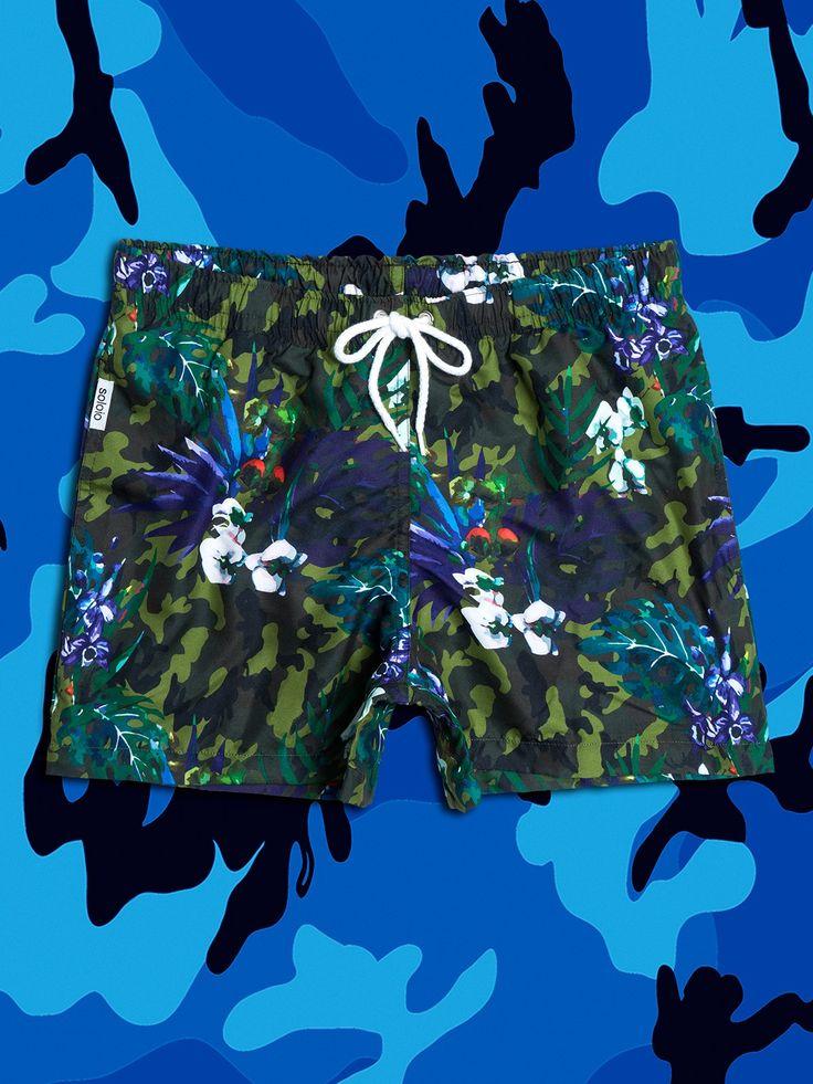 Bañador estampado con diseño de flores en color azul sobre print de camuflaje en tonos verdes. Dos bolsillos laterales y cinturilla elástica. www.soloio.com  #shoponline #beachwear #beachtowel #towel #print #blue #summercollection #summer #print #green #kiwi #camo