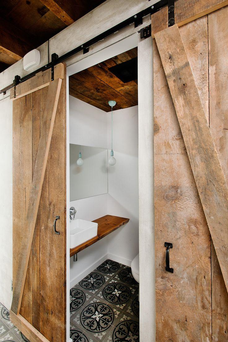 Do koupelny se v přízemí vstupuje posuvnými dveřmi z recyklovaného dřeva.