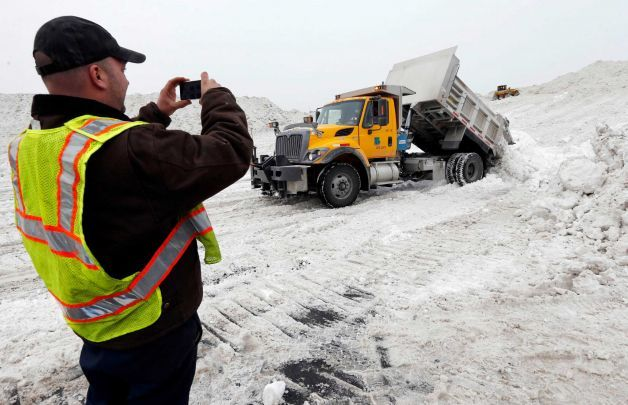"Rick Chestnet, who works for the Pennsylvania Department of Transportation,  records a video on his cell phone as a department truck unloads snow at a ""snow farm"" in Boston, Saturday, Feb. 14, 2015. Crews from around the region have worked urgently to remove the massive amounts of snow that has clogged streets and triggered numerous roof collapses ahead of yet another winter storm due to arrive on Saturday. Photo: Michael Dwyer, AP / AP"
