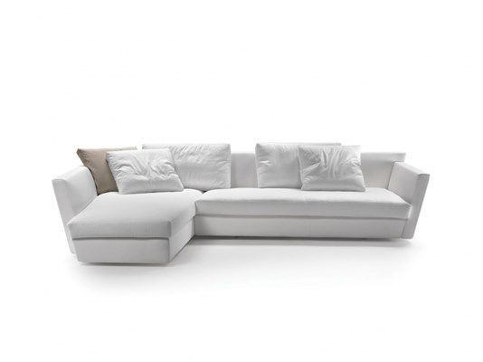 A project with a dynamic, deconstructed design, like the works of architecture of the visionary American talent. A component sofa, visually light, the result of the composition of specific volumes where Euclidean geometry is cast aside. The upholstered back is high and inclined, while the single soft cushion is trapezoidal in form, combined with a chaise longue element that also has an asymmetrical form. The armrests are padded or in painted metal. Unusual angles and thicknesses, with no…