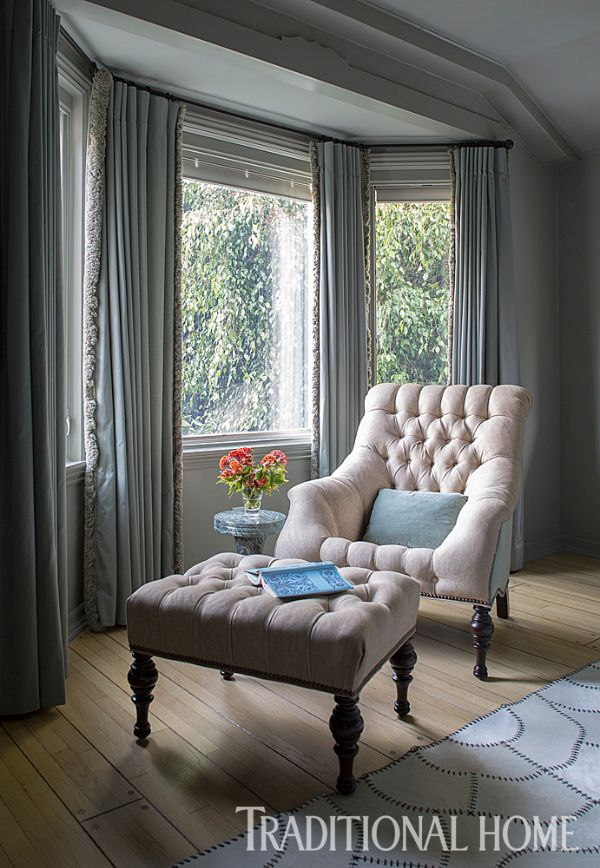 In A Light Filled Bump Out A Tufted Chair And Ottoman