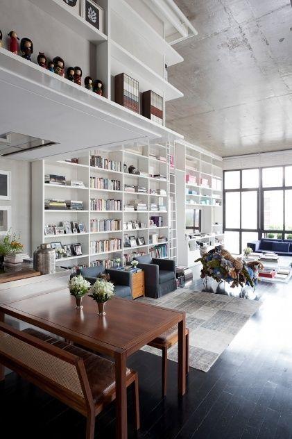 Desse ângulo é possível observar o prolongamento da estante no trecho sobre a cozinha, formando uma quina com prateleiras muito úteis. O grande destaque da arquitetura é a estante expondo objetos, livros, discos e filmes.