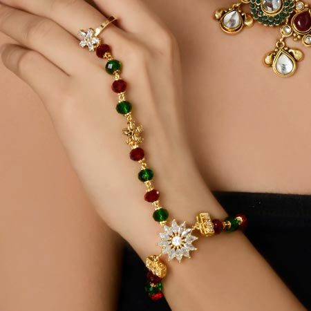 Trendy red and green finger ring bracelet is a bracelet which you can wear with your any semi-Indian dress as it is embellished with diamonds in the center piece of the bracelet which is attached with red and green pearls and that of diamond ring is also attached with red and green pearls string with diamonds in the center of the string. #BeautifulRingBracelet