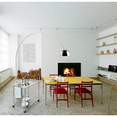ARCO Floor Lamp Stands Above This Cozy Dining Room Featuring White Walls And A Fireplace
