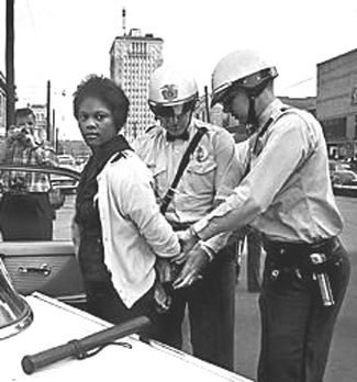 Birmingham police arresting Mattie Howard, a Parker High School student, during mass protests in 1963.