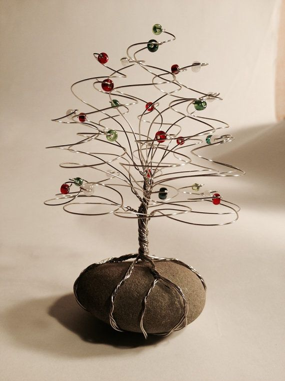 Christmas Tree Sculpture  Foliage: Glass beads, Red, Green & White Wire: Silver Base: stone Size: 5 inch high by 3 inches wide  Tree Sculptures  Elegantly handmade tree sculptures are skillfully, beaded by hand and weaved together to form a tree with unique character, with twisted roots that encircle and anchor the tree to a stone foundation. Tree sculptures are created using Glass beads and wire. To preserve surfaces the underside of the stone foundation is covered with a protective material…