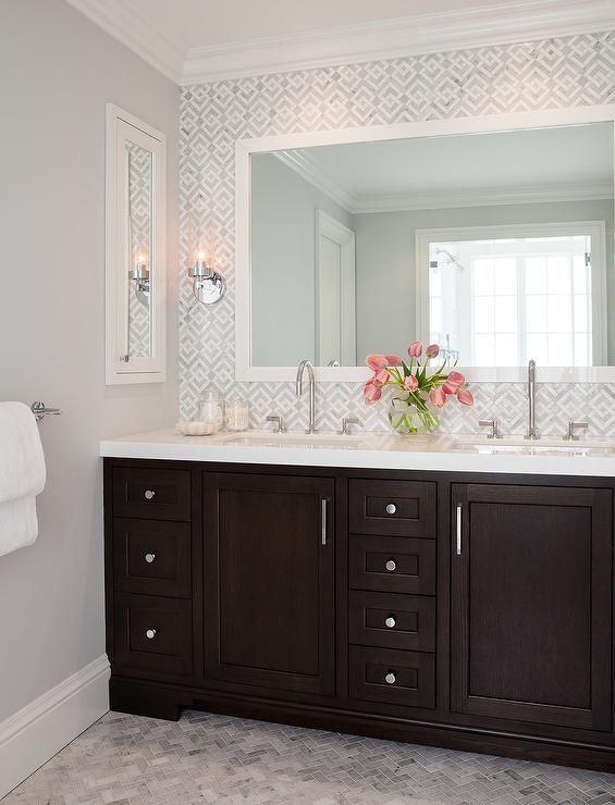 Fabulous bathroom boasts an espresso dual washstand topped with white quartz fitted with his and her sinks and polished nickel gooseneck faucets under a white Parsons mirror lining a white and gray geometric marble tiled backsplash.
