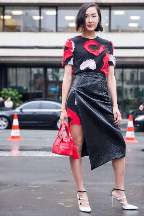 Fashion blogger Chriselle Lim wearing a black, red and white patterned dress with a leather high-slit midi skirt, as well as white strappy pointed-toe pumps and a red bag at Fall 2016 Paris Couture Week.