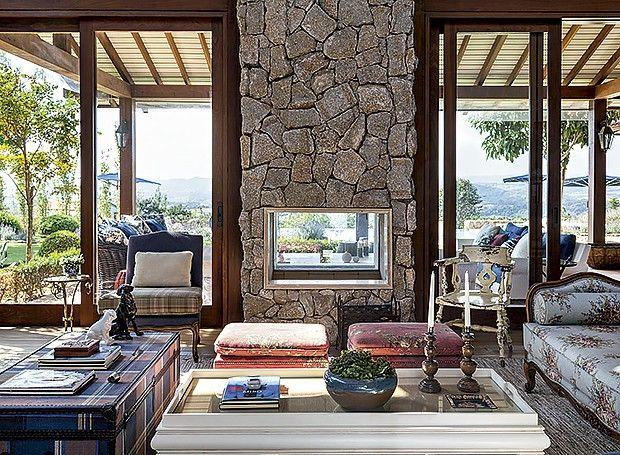 Sala de estar: com revestimento de pedras brutas irregulares, o espaço tem um baú da Artefacto B&C, utilizado como aparador. Pufes individuais da Christie Móveis servem de assento e mesa lateral (Foto: Evelyn Muller/ Divulgação)