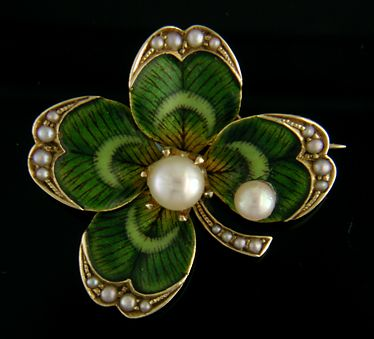 A beautifully enameled Victorian lucky clover brooch.  The edges of the petals and stem are gold and set with small graduated pearls.  A larger pearl is set in the center and a second rests on a petal like a small dew drop.  Created by Bippart, Griscom & Osborn in 14kt gold, circa 1900.