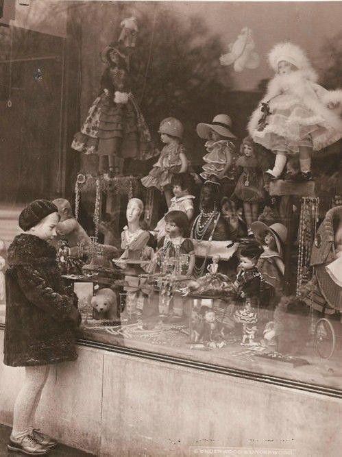 Bir oyuncakçı dükkanı vitrini ve ona bakan çocuk  yıl 1920