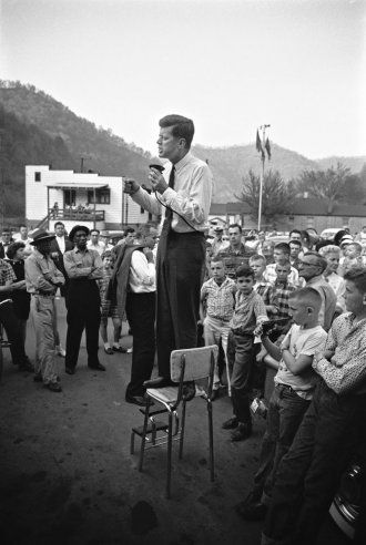 John F. Kennedy gives a speech while standing on a kitchen chair in Logan County, West Virginia, 1960.