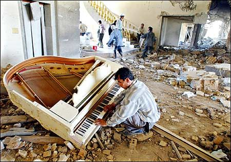 A man plays piano while others loot one of Saddam Hussein's former palaces in Baghdad (Saturday, May 3, 2003)  Source: Alexander Zemlianichenko (AP)