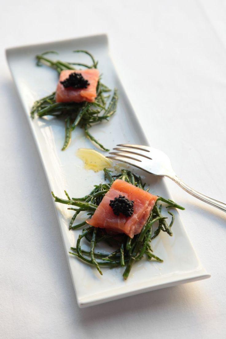 Bereiden:Spoel de zeekraal, verwijder de harde gedeelten. Snijd de zalmhaas in 4 blokjes. Wok de zeekraal kort in olijfolie. Kruid met zwarte peper. Warm de blokjes zalm kort op in de oven.Leg de zeekraal op een schaaltje of lepel. Leg de zalm erop en garneer met viseitjes.Tip:Voeg geen zout toe, de zeekraal is al zout van smaak.