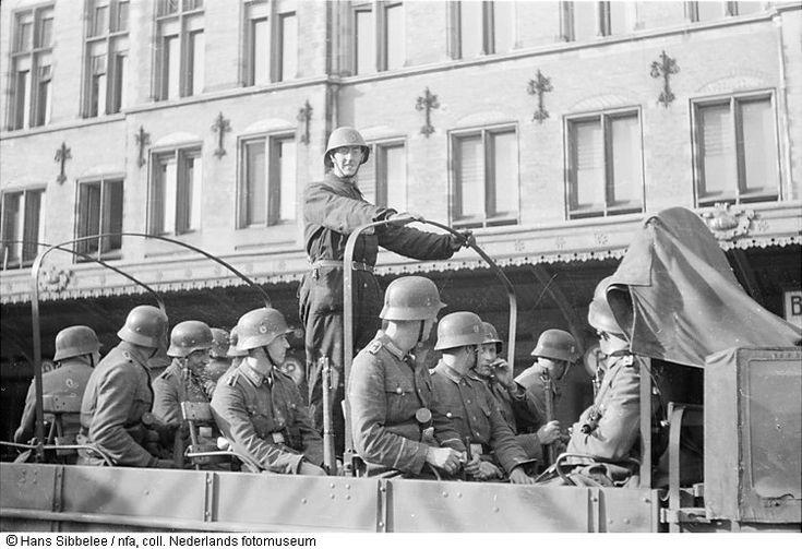Aan de voorzijde van het Centraal Station zitten Duitse soldaten in een open vrachtwagen, Amsterdam (mei 1945)