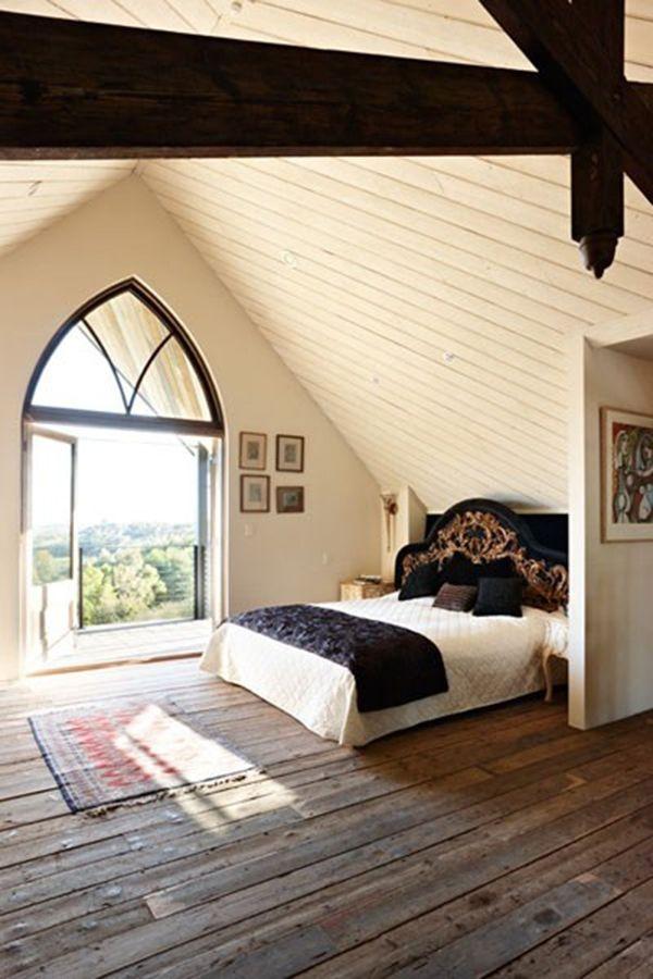 Hier zie je een slaapkamer, die is gemaakt op een verdieping in een oude kerk. Door het grote, ouderwetse raam heb je een prachtig uitzicht op het landschap.