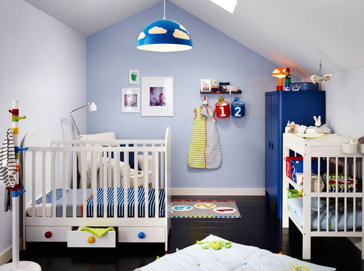 A nursery with a white crib with floor drawers and a changing table. Combined with a blue wardrobe.