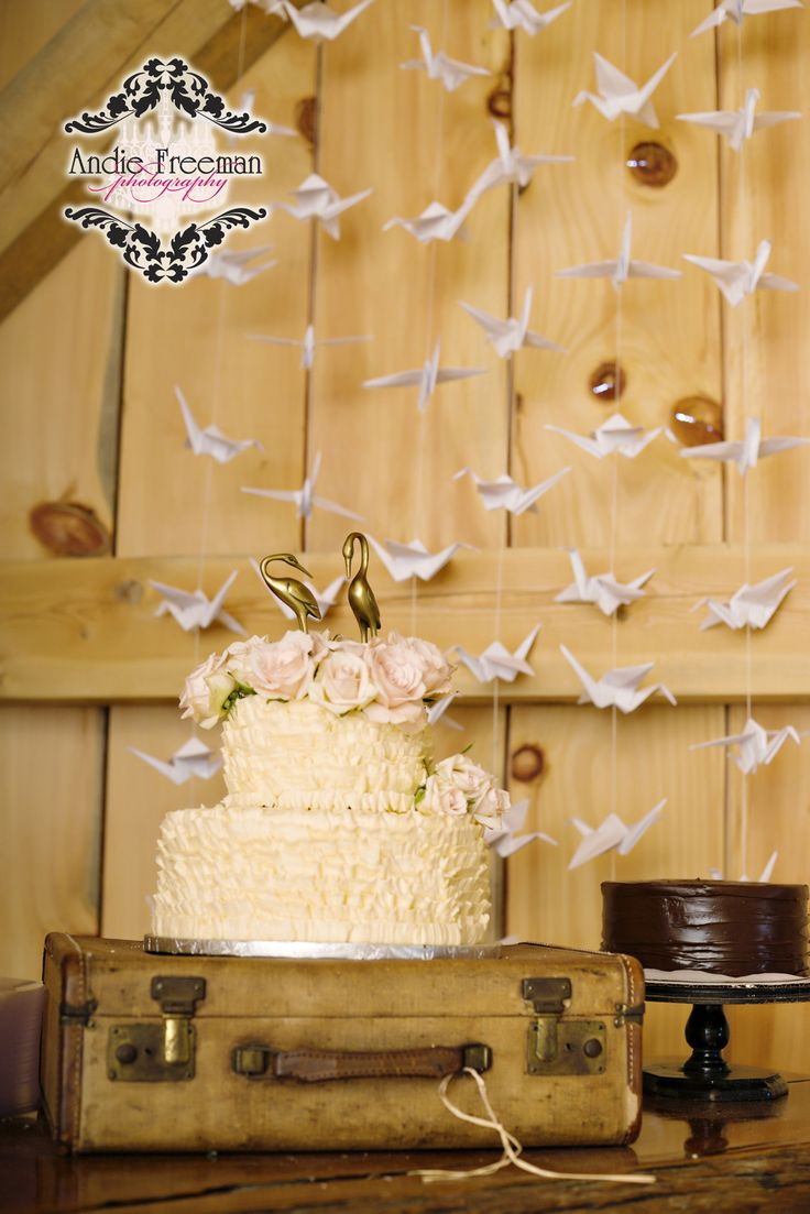 Country barn wedding vintage cake with roses and crane cake topper and ruffled icing displayed on vintage suitcase