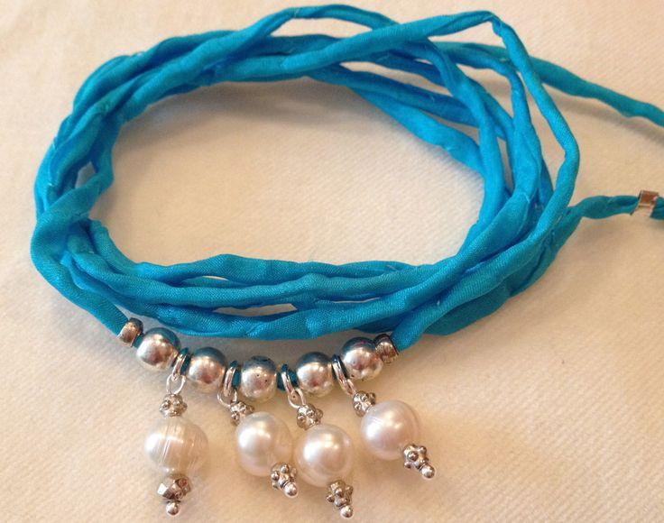 """Türkisblaues Meer und der Zauber glänzendweißer Perlen: Das Seiden-Armband """"Malediven-Liebe"""" spielt mit weißen Süßwasser-Perlen und lässt sie luftig-leicht am Handgelenk aufliegen.Handgefärbtes, blaues Seiden-Armband mit mehreren versilberten Elementen und weißen Süßwasser-Perlen.Länge: 86 cm"""