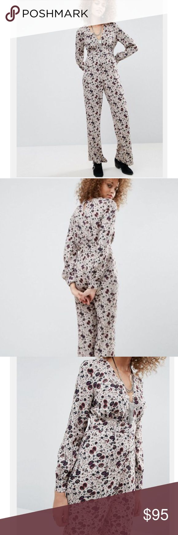 Free People Floral Jumpsuit Fulfill all your bohemian dreams with this show-stopping Free People Jumpsuit featuring a lightweight printed fabric, plunge neck, fitted empire band, flared leg, and button-keyhole back. Made of 52% Viscose, 48% Rayon in a Size 0. New! Never worn or washed. Retail $252. Free People Dresses