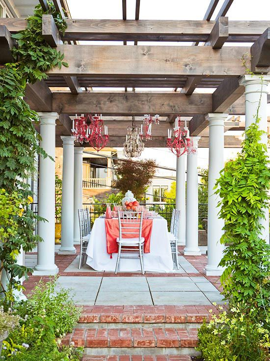 Pergolas are perfect for creating little garden getaways. Here's a great example of how you can use a pergola to create an outdoor dining room. The cozy space features lighting, an easy-to-clean brick floor, and room for plenty of seating. It's all done over a simple brick-and-paver patio.