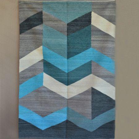 Alfombra o carpeta tejida en telar de peine con lana pura de oveja hilada con rueca y teñida a mano. Urdimbre de algodón y trama de lana. Suave en su textura y definida en su diseño sobrio.