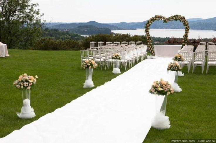 Arco floreale per un matrimonio con cerimonia all'aperto e decorazioni eleganti. Tappetto bianco e composizioni di rose in vasi alti