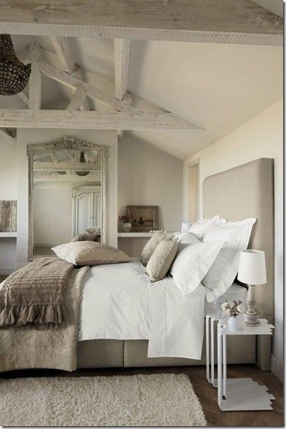 Whitewashed beams on the ceiling and texture in the bedlinens and area rug create a gorgeous neutral bedroom