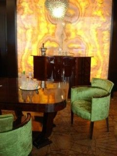 Stylish bar section in any luxurious apartment: Art Deco envelope bar with armchairs and onyx wall..