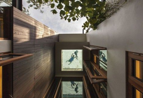 Stunning view from inside home, looking up to the upper deck glass bottom pool.  Brings to mind the thought of an aquarium, except for people instead of fish. #creative #design #interior #architecture #swimmingpool