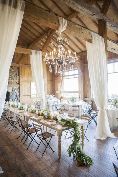 This reception style is the definition of rustic chic. Wood interiors and a stone hearth play home to an enchanting chandelier, gauzy white curtains, and an elegantly exposed head table showcasing a stunning swath of foliage.