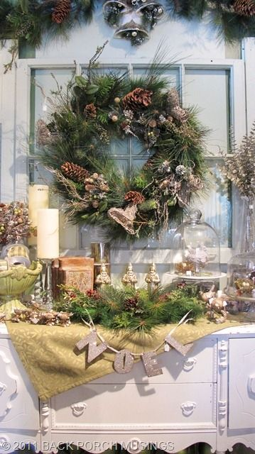 love this tabletop display. At first I thought it was a mantle. All the layers pull together with the gold  tones. I like the window over the buffet and the wreath added.