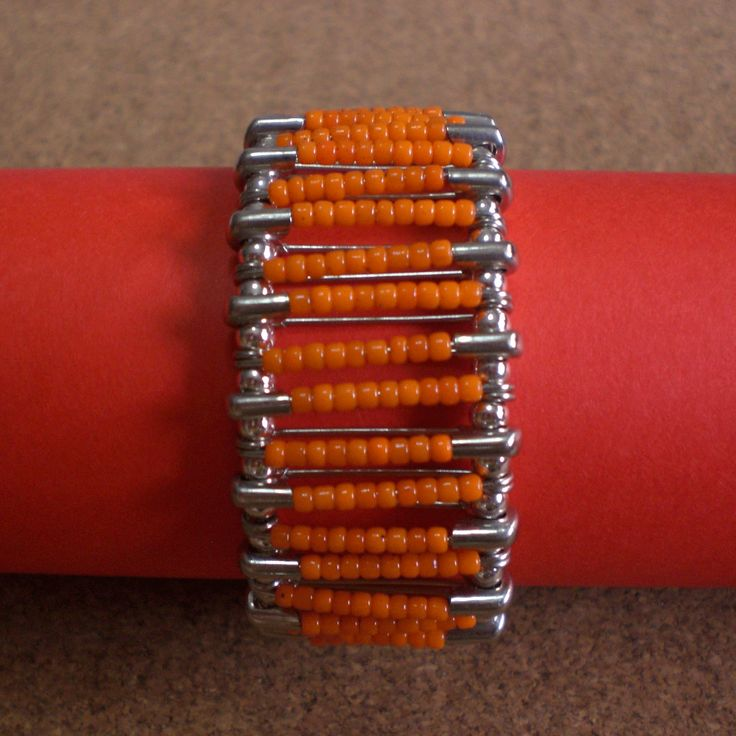 Bracelet made using safety pins with orange plastic beads. Connected with silver round beads.