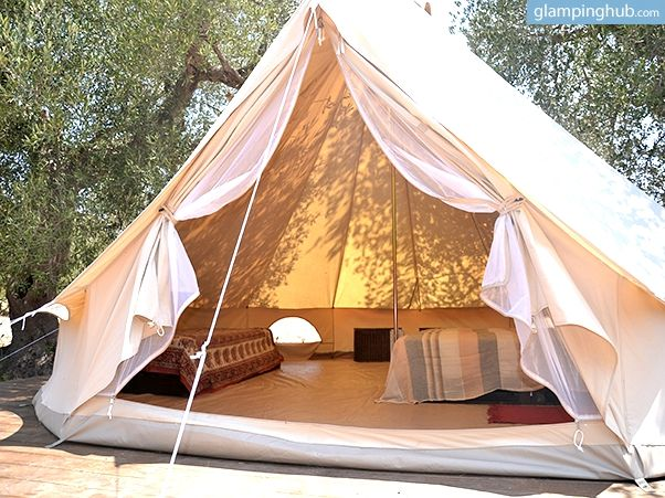 Witness the rolling Salentini hills where the traditional rural countryside and beautiful blue sea meet at this glamping site.  Take in the sites in comfort at night in a spacious tent with beds under centenarian olive trees that keep your room nice and cool.