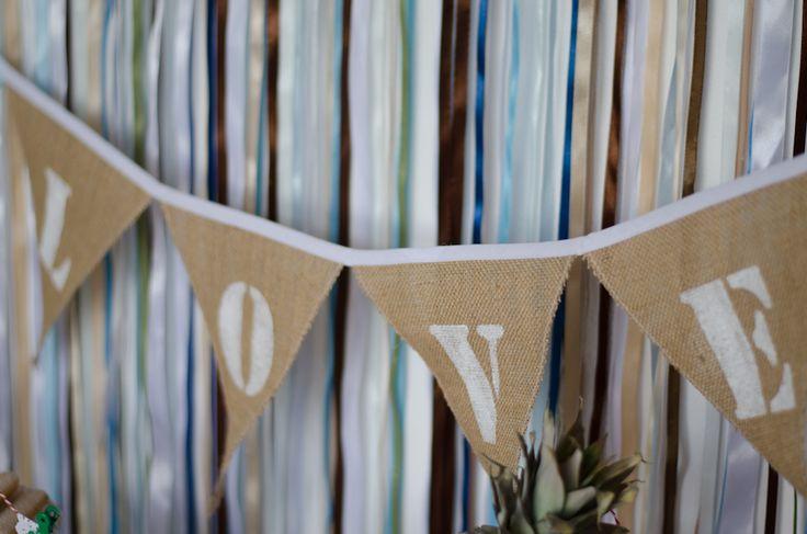 Love is in the air! Hippe Jute slinger, met de letters LOVE. Deze slinger kun je gebruiken tijdens je fotoshoot, aan je stoelen bij de ceremonie, boven de receptietafel, op het feest aan de muur of buiten tussen twee bomen. De slinger is prachtig afgewerkt met band en zelfs ieder vlaggetje is apart gestikt om rafelen tegen te gaan. De vlaggen zijn bruin jute en het band en de letters zijn wit.