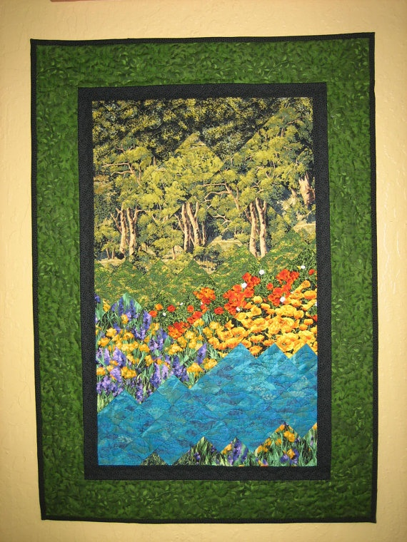 This fabric art quilt depicts turquoise water surrounded by yellow, orange and purple flowers set in front of a forest of spring trees. Turquoise Waters Art Quilt Fabric Wall Hanging