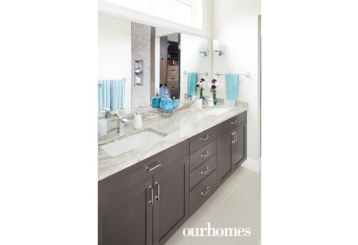 """His-and-hers seamless sinks make this streamlined bathroom a breeze to clean, one of the design prerequisites for the home.    See more of this home in """"She Loved this Chandelier and Built a House to Suit It"""" from OUR HOMES Wellington County Orangeville Caledon, Summer 2017: http://www.ourhomes.ca/articles/build/article/she-loved-this-chandelier-and-built-a-house-to-suit-it"""
