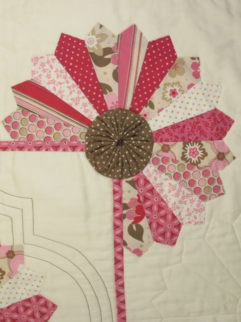 Dresden plate or Starburst w/yo yo used on a corner or a quilt.  How novel....