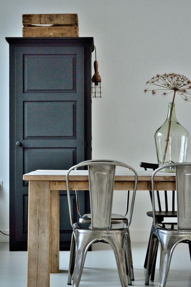 .Mooie combinatie van blank houten tafel grijze muur en stoelen zwarte kast